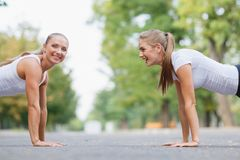 Fitness girls doing push-ups outdoors on a park background. Sporty girls. Workout concept. Copy space. stock photography