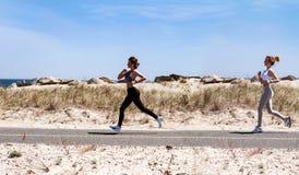 Fitness girls running on beach. Fitness women running on beach. Happy girls women jogging outdoors Stock Image