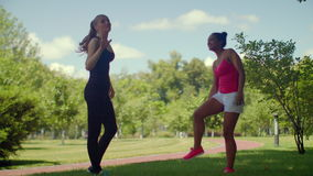 Fitness girls talking in park at summer day. Young female friends talking stock video footage