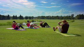 Fitness group doing crunches with personal trainer. Outdoor fitness class stock video footage