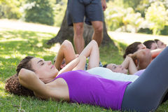Fitness group doing sit ups in park with coach stock image