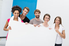 Fitness group at the gym holding a blank card Royalty Free Stock Image