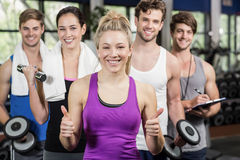 Fitness group lifting dumbbells and showing thumbs up Stock Photos
