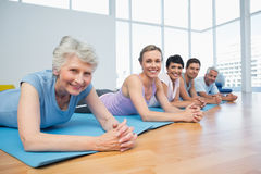 Fitness group lying in row at yoga class Stock Image