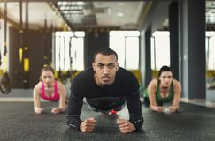 Fitness group plank training indoors. Fitness group doing plank workout training with coach indoors. Young men and women making exercise at gym. Healthy stock photo