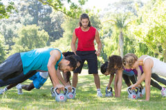 Fitness group planking in park with coach Stock Images