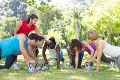 Fitness group planking in park with coach Stock Photography
