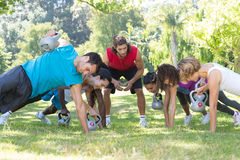 Fitness group planking in park with coach Royalty Free Stock Images