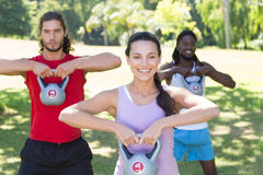 Fitness group working out in park with kettle bells Stock Photography