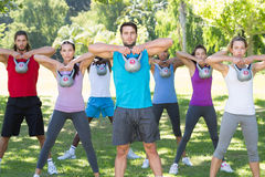 Fitness group working out in park with kettle bells Royalty Free Stock Photography