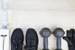 Fitness grove, drinking water bottle, sport shoes, dumbbells, white towel and headphone on wooden background Stock Photos