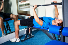 Fitness guy lying on bench and exercising Stock Images