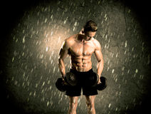 Fitness guy with weight showing muscles Stock Photos