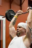 Fitness gym. Fitness training, cool tattooed man exercising in the gym Stock Photography