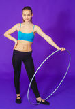 Fitness and gym concept - young sporty woman with hula hoop at gym.on a blue background Stock Photography