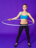 Fitness and gym concept - young sporty woman with hula hoop at gym.on a blue background Royalty Free Stock Photos