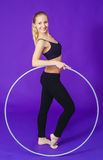Fitness and gym concept - young sporty woman with hula hoop at gym.on a blue background Stock Photo