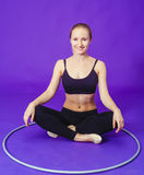 Fitness and gym concept - young sporty woman with hula hoop at gym.on a blue background Stock Image
