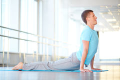 Fitness in gym. Healthy guy doing stretching exercise in gym Royalty Free Stock Photos
