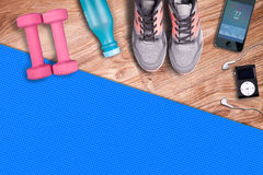 Fitness gym mat and light pink dumbbells. Fit equipment shoes and music player. Stock Image