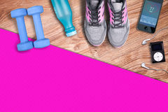 Fitness gym mat and light pink dumbbells. Fit equipment shoes and music player. Royalty Free Stock Photos