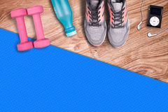 Fitness gym mat and light pink dumbbells. Fit equipment shoes and music player. Royalty Free Stock Photography
