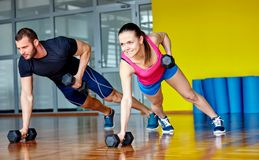 Fitness gym. Gym men and women push-up strength pushup with dumbbell in a fitness workout royalty free stock images