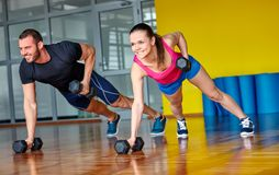 Fitness gym. Gym men and women push-up strength pushup with dumbbell in a fitness workout Royalty Free Stock Photography