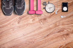 Fitness gym and running equipment. Dumbbells and running shoes, analog stopwatch and music player. Time for fitness and run. Sport accessories on the wooden Royalty Free Stock Images
