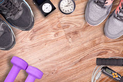 Fitness gym and running equipment. Dumbbells and running shoes, analog stopwatch and music player. Time for fitness and run. Sport accessories for women on the Royalty Free Stock Photography