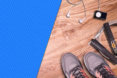 Fitness gym and running equipment. Stopwatch and running shoes, jumping rope and music player. Time for fitness. Royalty Free Stock Photos