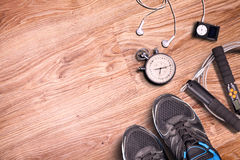 Fitness gym and running equipment. Stopwatch and running shoes, jumping rope and music player. Time for fitness. Sport running accessories on wood flor and gym Royalty Free Stock Images