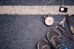 Fitness gym and running equipment. Stopwatch and running shoes, jumping rope and music player. Time for fitness. Sport running accessories on asphalt Stock Photography