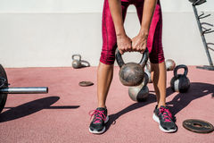 Fitness gym woman weightlifting kettlebell weight. Woman weightlifting kettlebell weight at outdoor fitness gym. Unrecognizable female athlete strength training Stock Photography