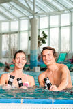 Fitness - gymnastics under water in swimming pool. Fitness - a young couple - man and woman - doing sports and gymnastics or water aerobics under water in Stock Images