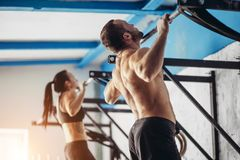 Fitness handsome man doing dipping exercise using rings in gym stock photo