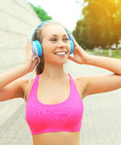 Fitness happy smiling woman with headphones listens to music in city, sport and healthy lifestyle Royalty Free Stock Images