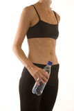 Fitness and Health. Beautiful young woman wearing workout clothes and holding a water bottle Royalty Free Stock Photo