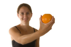Fitness and Health. Beautiful young woman wearing workout clothes and holding an orange.  Focus on orange Royalty Free Stock Photo