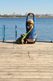 Fitness, health, yoga. Leisure and relaxation in the coast, the woman spends his free time, she sits on the pier overlooking the water and city in the distance Stock Image