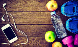 Fitness, healthy and active lifestyles Concept, Bottle of water,. Dumbbells, sport shoes, smartphone with headphone and apples on wood background. copy space Royalty Free Stock Photography