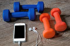 Fitness, healthy and active lifestyles Concept, dumbbells, sport shoes and smartphone with headphone on wood background royalty free stock photo