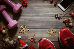 Fitness, healthy and active lifestyles love concept, dumbbells,. Sport shoes, skipping rope or jump rope and smart phone with Christmas decoration items on wood Royalty Free Stock Images