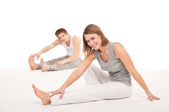 Fitness - Healthy couple stretching on white. Fitness - Healthy couple stretching after training on white background Royalty Free Stock Images