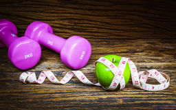 Fitness, healthy eating, dieting concept, dumbbells,  apples. Fitness, healthy eating and dieting concept, dumbbells,  apples and measuring tape Stock Photo