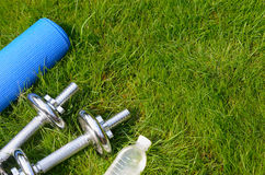 Fitness and healthy lifestyle concept, sport shoes, dumbbells, bottle of water and mat on grass Stock Photography
