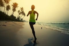 Woman running on tropical beach during sunrise stock photo