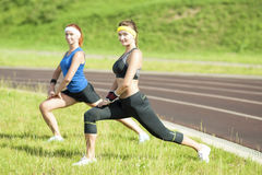 Fitness and Healthy LifestyleTwo Caucasian Girlfriends Having Body Stretching and Trunk Bending Ideas and Concepts. Two Caucasian Stock Image