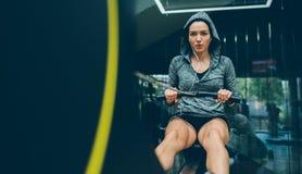 Fitness, het bodybuilding, mensen, gezond levensstijl en sportconcept De mooie geschikte donkerbruine vrouw doet binnen oefeninge royalty-vrije stock foto's