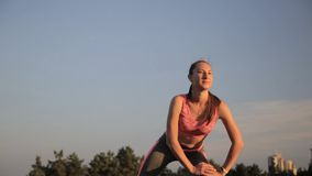 Fitness hipster girl in fashion sportswear doing yoga fitness exercise in the street, outdoor sports. Fitness hipster girl in fashion sportswear doing yoga stock footage